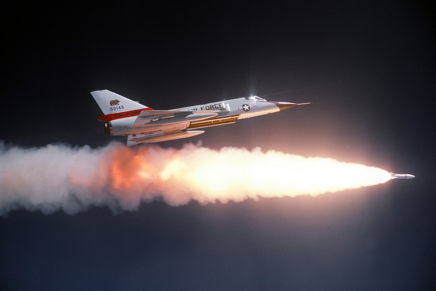 An air-to-air right side view of an F-106 Delta Dart aircraft after firing an ATR-2A missile over a range. An auxiliary fuel tank is on each wing. The aircraft is assigned to the 194th Fighter Interceptor Squadron, California Air National Guard. After 1970, most Darts were flown by the Air Guard in North American Air Defense roles