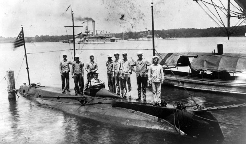 Holland (SS-01), at the US Naval Acadamy, Annapolis, MD., summer of 1905. The crew on deck are, L to R: Harry Wahab, chief gunner's mate; Kane; Richard O. Williams, chief electrician; Chief Gunner Owen Hill, commanding; Igoe; Michael Malone; Barnett Bowie, Simpson, chief machinist mate, and Rhinelander. The two vessels on the right are monitors. The inboard vessel has only one turret and is probably one of 3 monitors: Arkansas (M-7), Nevada(M-8) or Florida (M-9). The outboard 2 turreted monitor is also one of 3 probables: Amphitrite (BM-2), Terror (M-4) or Miantonomah (BM-5).