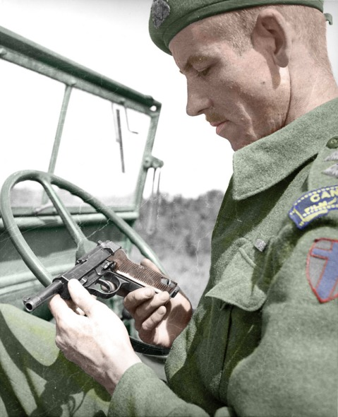 canadian soldier checking out a captured P38 during WWII