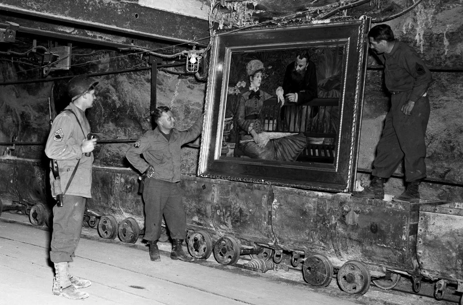 """Merkers, Germany U.S. Soldiers examine a famous painting, """"Wintergarden,"""" by the French Impressionist Edouard Manet, in the collection of Reichbank wealth, SS loot, and paintings removed by the Nazis from Berlin to a salt mine vault. The 90th Div, U.S. Third Army, discovered the gold and other treasure. 04/15/45 Photographer: Cpl. Ornitz RG-111-SC-203453-5.tif"""