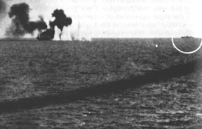 The stricken Gambier Bay on fire, left, with Yamato, circled, right