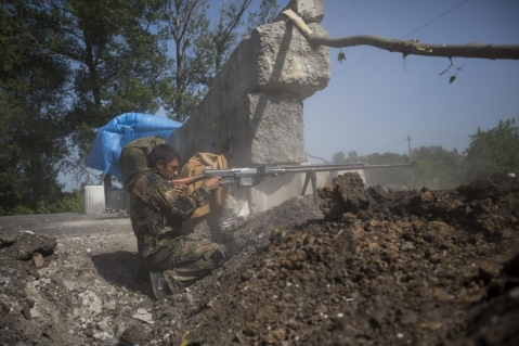 A pro-Russian militant test-fires an anti-tank weapon preparing to fight against Ukrainian government troops at a checkpoint blocking the major highway which links Kharkiv, outside Slovyansk, eastern Ukraine, Sunday, May 18, 2014. (AP Photo/Alexander Zemlianichenko)