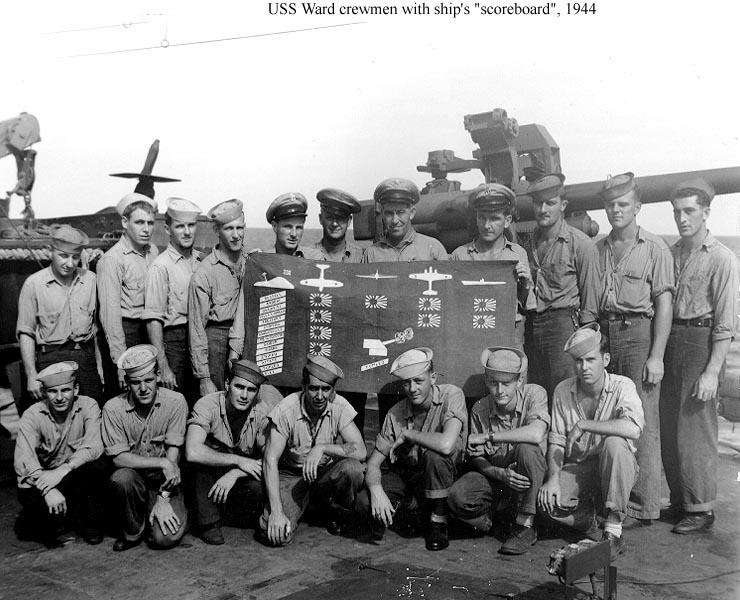"""Sansapor, Dutch New Guinea, falls to the Allied Forces, July 30, 1944. One might almost say - Sansapor falls to the boys from St. Paul, Minn. - as all but two of these men come from that city and the entire group has shipped together since Pearl Harbor, with the actions and results shown on their banner. As a matter of fact, they are believed to have fired the first offensive shot of the war in the Pacific, while on patrol against Japanese subs."" Note the more than a dozen landings credited on the scoreboard on the left side as well as two subs and several planes. They are L/R: (bottom row) J.L. Spratt, MM2/c; A.J. Fink, CM2/c; O.S. Ethier, MM1/c; C.W. Fenton, BM1/c; D.R. Pepin, SM1/c; J.G. LeClair; SOM2/c; F.V. Huges, SOM2/c. (Top Row) R.B. Nolde, SF1c; W.G. Grip, BM2c; H.F. Germarin, S1c; H.J. Harris, MM1c; H.K. Paynter, CMoMM; J.K. Lovsted, CMMM; W.H. Duval, CCS, (of San Diego); I.E. Holley, CSK (of Los Angeles); W.S. Lehner, SC1c; F.J. Bukrey, CM1c; and F.L. Fratta, MM1c."""