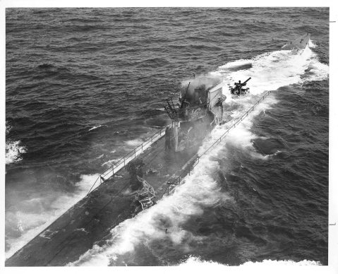 """Official Caption: """"NAZI SUBMARINE SUNK BY THE FAMED CUTTER SPENCER: Effect of the U.S. Coast Guard Cutter SPENCER'S fire are visible in this closeup shot of the U-Boat, taken as the battle raged. The Nazi standing by the stanchion amidships disappeared a moment after this picture was taken by a Coast Guard photographer. The U-Boat had been trying to sneak into the center of the convoy."""" Date: 17 April 1943 Photo No.: 1512 Photographer: Jack January? Description: The """"Nazi"""" mentioned in the above caption was probably in fact a member of the Coast Guard boarding team--one of the first Americans to board an enemy man-of-war underway at sea since the War of 1812."""