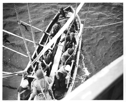 """Official Caption: """"OFF TO RESCUE THEIR BEATEN FOES: A pulling boat leaves the side of a Coast Guard combat cutter to rescue Nazi seamen struggling in the mid-Atlantic after their U-Boat had been blasted to the bottom by the cutter's depth charges. Two Coast Guard cutters brought 41 German survivors to a Scottish port."""" Date: 17 April 1943 Photo No.: 1516 Photographer: Jack January Description: The men in this pulling boat were in fact a trained boarding team led by LCDR John B. Oren (standing in the stern and wearing the OD helmet) and LT Ross Bullard (directly to Oren's left). With the assistance of the Royal Navy they had practiced boarding a submarine at sea in order to capture an Enigma coding machine and related intelligence material. They were forced to take a pulling lifeboat when the Spencer's motor lifeboat was damaged by friendly fire."""