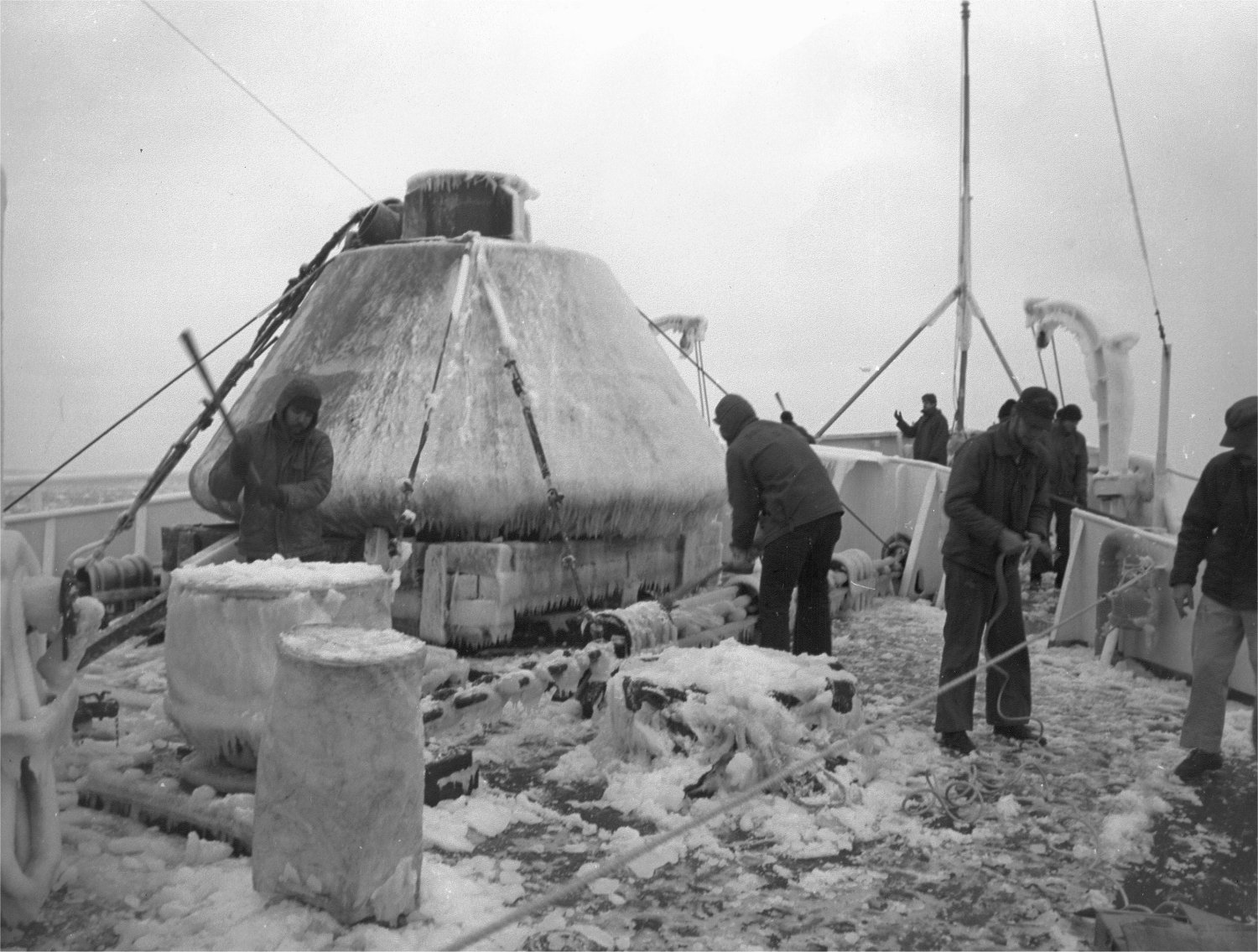 USCGC Southwind (WAGB-280) crew members chip away at ice while in Baffin Bay, November 1970. Note the Apollo capsule on the deck. USCG Photo scanned from Southwind's Arctic East 70 scrapbook.