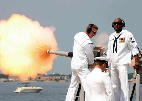 Gunners Mates First Class (GM1) Ronnie Owens and Richard Ashley fire a 40mm saluting cannon in honor of the Governor of the State of Florida from the destroyer USS Momsen in 2004. US Navy photo.