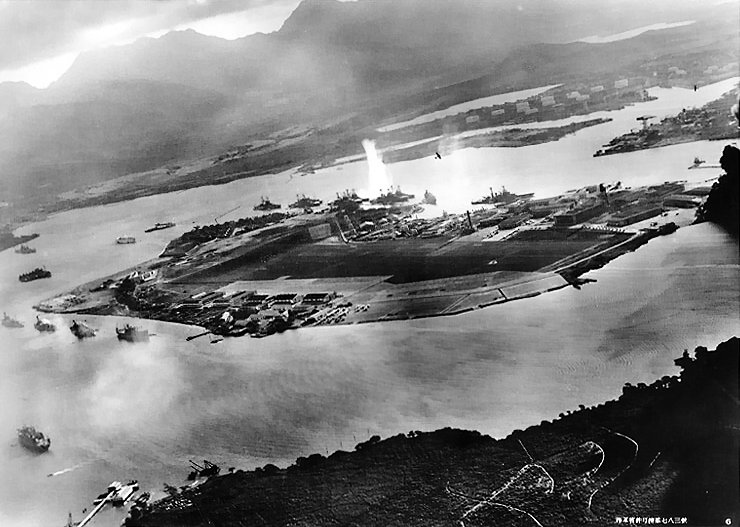 Photograph taken from a Japanese plane during the torpedo attack on ships moored on both sides of Ford Island shortly after the beginning of the Pearl Harbor attack. View looks about east, with the supply depot, submarine base and fuel tank farm in the right center distance. A torpedo has just hit USS West Virginia on the far side of Ford Island (center). Other battleships moored nearby are (from left): Nevada, Arizona, Tennessee (inboard of West Virginia), Oklahoma (torpedoed and listing) alongside Maryland, and California. On the near side of Ford Island, to the left, are light cruisers Detroit and Raleigh, target and training ship Utah and seaplane tender Tangier. Raleigh and Utah have been torpedoed, and Utah is listing sharply to port. Japanese planes are visible in the right center (over Ford Island) and over the Navy Yard at right. U.S. Navy planes on the seaplane ramp are on fire. Japanese writing in the lower right states that the photograph was reproduced by authorization of the Navy Ministry. Official U.S. Navy photograph NH 50930.