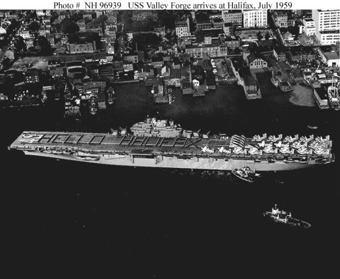 """USS Valley Forge (CVS-45) Arrives at Halifax, Nova Scotia, with crewmen in formation spelling out """"HELLO HALIFAX"""" on her flight deck, 10 July 1959.Valley Forge, flying the flag of Rear Admiral John S. Thach and commanded by Captain William M. McCormick, was accompanied by the rest of Task Force ALFA, including seven destroyers and two submarines. Altogether, about 4000 U.S. Navy sailors were in Halifax for the six-day visit. At this point she has the deck of the Franklin installed. Photo #: NH 96939"""