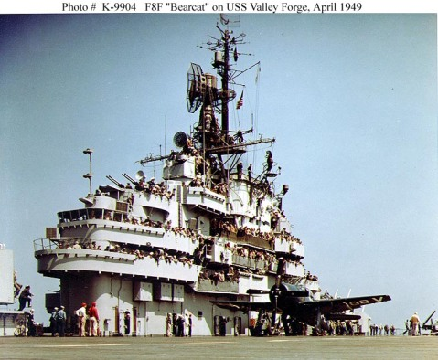 """View of the carrier's island, with members of the American Ordnance Association visiting on board, while the ship was operating near Long Beach, California, 27 April 1949. An F8F-2 """"Bearcat"""" fighter is parked alongside the island.Note large SX radar antenna atop the tripod mast, and many onlookers standing on the island walkways. Photo #: 80-G-K-9904 (Color)"""