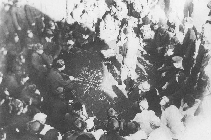 Lieutenant Ichiro Kitajima, group leader of the Imperial Japanese Navy aircraft carrier Kaga's Nakajima B5N bomber group, briefs his flight crews about the Pearl Harbor raid, which will take place the next day. A diagram of Pearl Harbor and the aircraft's attack plan is chalked on the deck. Photo Chihaya Collection via Wenger via Wiki