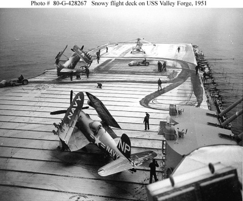 """USS Valley Forge (CV-45) Crewmen use flight deck tractors with power brooms to sweep snow from the carrier's flight deck, during operations off Korea, circa early 1951.Plane parked in the foreground is a F4U-4 """"Corsair"""" fighter. Those on the forward flight deck are an AD """"Skyraider"""" attack plane and a HO3S helicopter. Photo #: 80-G-428267"""