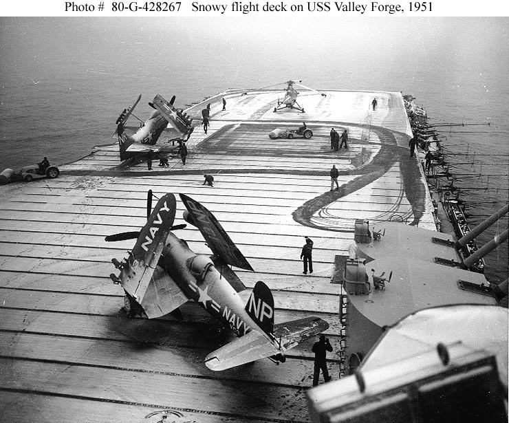 "USS Valley Forge (CV-45) Crewmen use flight deck tractors with power brooms to sweep snow from the carrier's flight deck, during operations off Korea, circa early 1951.Plane parked in the foreground is a F4U-4 ""Corsair"" fighter. Those on the forward flight deck are an AD ""Skyraider"" attack plane and a HO3S helicopter. Photo #: 80-G-428267"