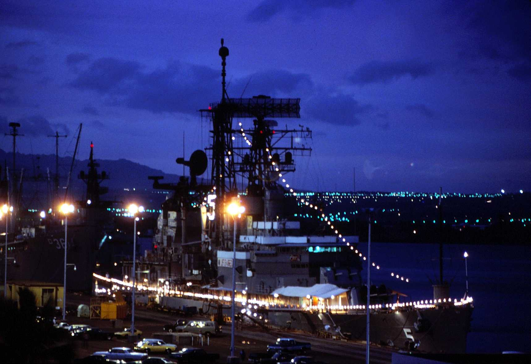 """Moored at Pearl Harbor, HI, 18 October 1979 with friendship lights lit. The """"Okie Boat"""" was on her way to San Diego for decommissioning after serving as Flagship of the Seventh Fleet for eleven years. This picture was taken from the roof of the old Enlisted Barracks, which has since been torn down. Photo by Tom Bateman via Navsource."""