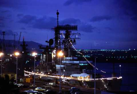 "Moored at Pearl Harbor, HI, 18 October 1979 with friendship lights lit. The ""Okie Boat"" was on her way to San Diego for decommissioning after serving as Flagship of the Seventh Fleet for eleven years. This picture was taken from the roof of the old Enlisted Barracks, which has since been torn down. Photo by Tom Bateman via Navsource."