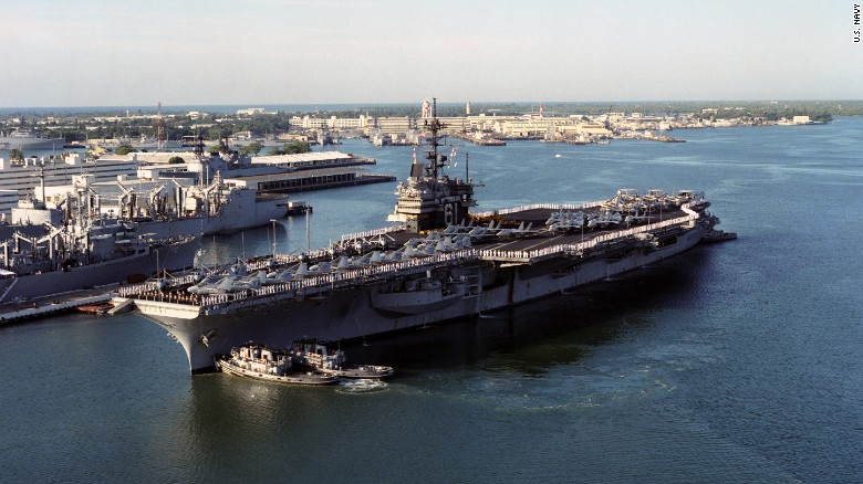 An aerial portside view of the US Navy (USN) Forrestal Class Aircraft Carrier USS RANGER (CV 61), with her Sailors manning the rails and aircraft of the Carrier Air Wing 2 (CVW-2) on her deck, as she is nudged into position by harbor tugs NIANTIC (YTB-781), NEODESHA (YTB-815), and WAXAHACHIE (YTB 814), at the pier on her arrival at Pearl Harbor Naval Base in Pearl Harbor, Hawaii (HI). USN Photo