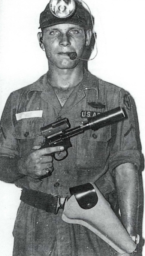 A soldier poses with his Tunnel Exploration Kit, consisting of a silenced .38 S&W, special holster and a mouth/teeth bite-switch activated headlamp.