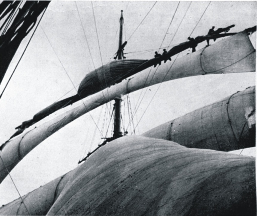 Out on the yardarm. Two of her crew, drafted by the old windjammer's huge lower yard, are bending the main course to its jackstay, by Roger Dudley from her 1932 voyage