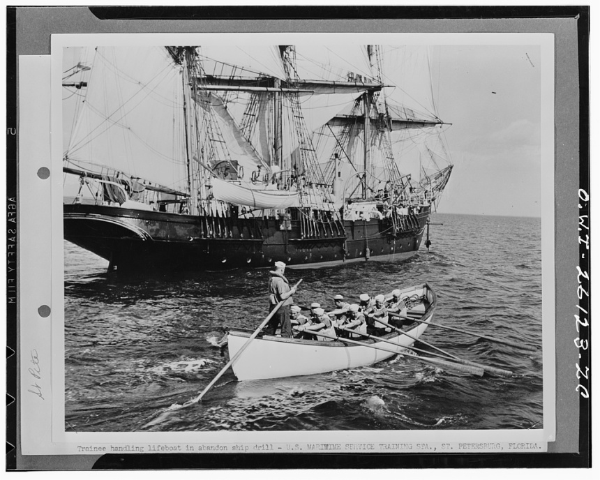 Trainee at the United States Maritime Service training station handling a life boat in an abandon ship drill-- note the Joseph Conrad