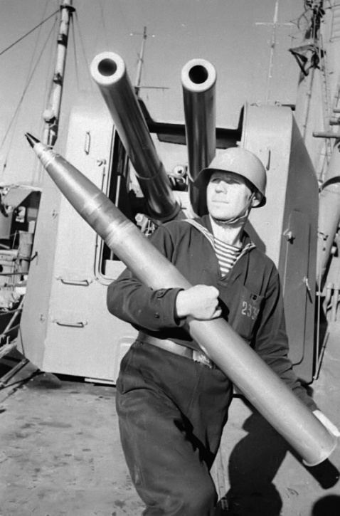 """Sailor on a cruiser of the Black Sea the """"Red Caucasus"""" in front of his 100mm flak piece"""