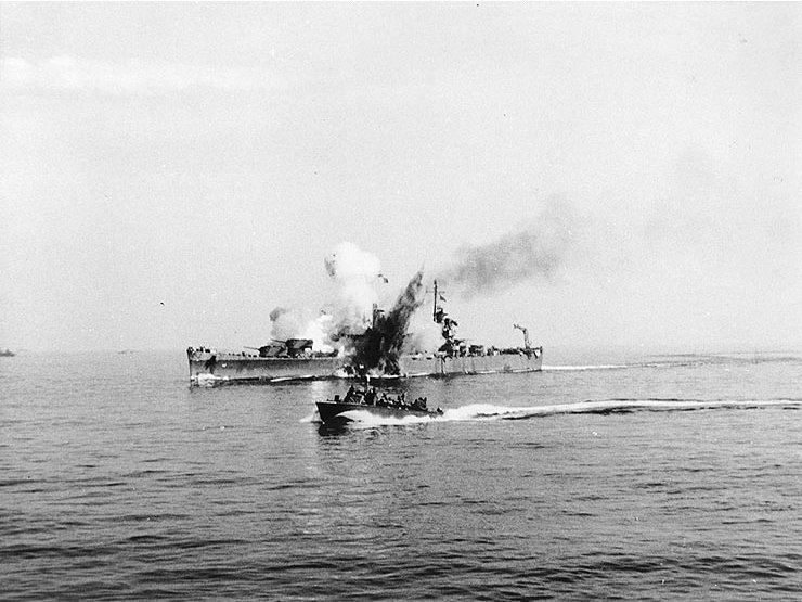 """USS Savannah (CL-42) is hit by a German radio-controlled glide bomb, while supporting Allied forces ashore during the Salerno operation, 11 September 1943. The bomb hit the top of the ship's number three 6""""/47 gun turret and penetrated deep into her hull before exploding. The photograph shows the explosion venting through the top of the turret and also through Savannah's hull below the waterline. A motor torpedo boat (PT) is passing by in the foreground. When you think that a pair of Fritz-X's completely destroyed the 45,000-ton Vittorio Veneto-class battleship Roma, its impressive that a 12,000-ton light cruiser survived such a hit."""