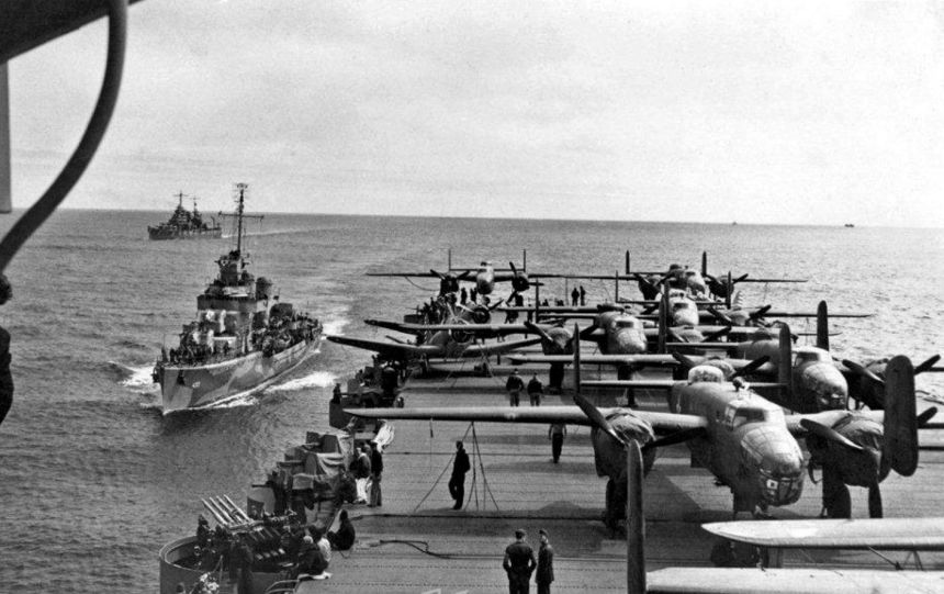 """View looking aft from the island of USS Hornet (CV 8), while en route to the mission's launching point. USS Gwin (DD-433) is coming alongside, as USS Nashville (CL-43) steams in the distance. Eight of the mission's sixteen B-25B bombers are parked within view, as are two of the ship's SBD scout bombers. Note midships elevator, torpedo elevator, arresting gear and flight deck barriers in the lower portion of the photo, and 1.1"""" quad anti-aircraft machine gun mount at left. Naval History & Heritage Command photo (# NH 53289)."""