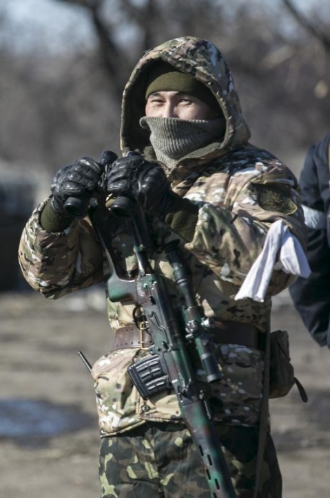 A fighter with the separatist self-proclaimed Donetsk People's Republic Army stands guard at a checkpoint along a road from the town of Vuhlehirsk to Debaltseve in Ukraine, in this file photo taken on February 18, 2015.   REUTERS/Baz Ratner
