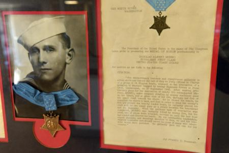 A display containing Petty Officer First Class Douglas Munro's Medal of Honor and accompanying citation hangs in Munro Hall at the U.S. Coast Guard Training Center in Cape May, N.J., (U.S. Coast Guard photo by Chief Warrant Officer John Edwards)