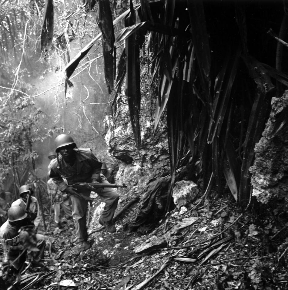 March 10, 1945: U.S. troops in the Pacific islands continued to find enemy holdouts long after the main Japanese forces had either surrendered or disappeared. Guam was considered cleared by August 12, 1944, but parts of the island were still dangerous half a year later. Here, patrolling Marines pass a dead Japanese sniper. These Marines may belong to the Fifty-second Defense Battalion, one of two black units sent to the Pacific. (Charles P. Gorry, AP Staff/AP Archives)
