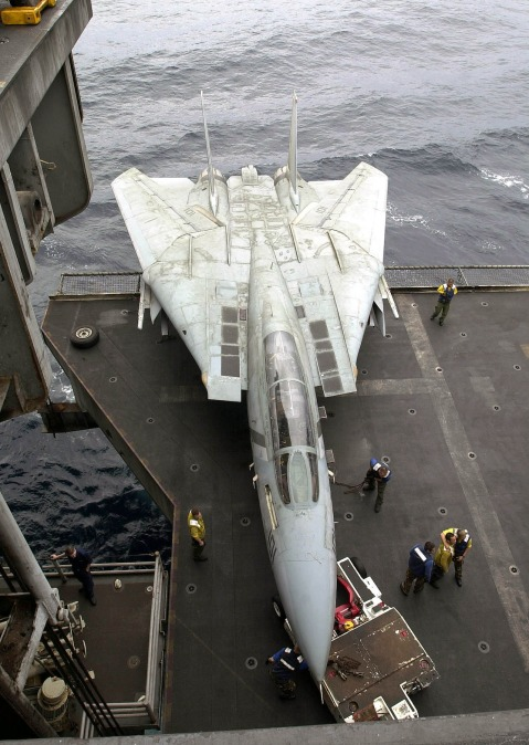 030413-N-0295M-004 Arabian Gulf (Apr. 13, 2003) -- Hanger Deck Crew move a F-14D Tomcat assigned to the ÒBounty HuntersÓ of Fighter Squadron Two (VF-2) onto one of four aircraft elevators aboard USS Constellation (CV 64).  Constellation and Carrier Air Wing Two (CVW-2) are deployed in support of Operation Iraqi Freedom.  Operation Iraqi Freedom is the multinational coalition effort to liberate the Iraqi people, eliminate Iraq's weapons of mass destruction and end the regime of Saddam Hussein.  U.S. Navy photo by Photographer's Mate 2nd Class Daniel J. McLain.  (RELEASED)