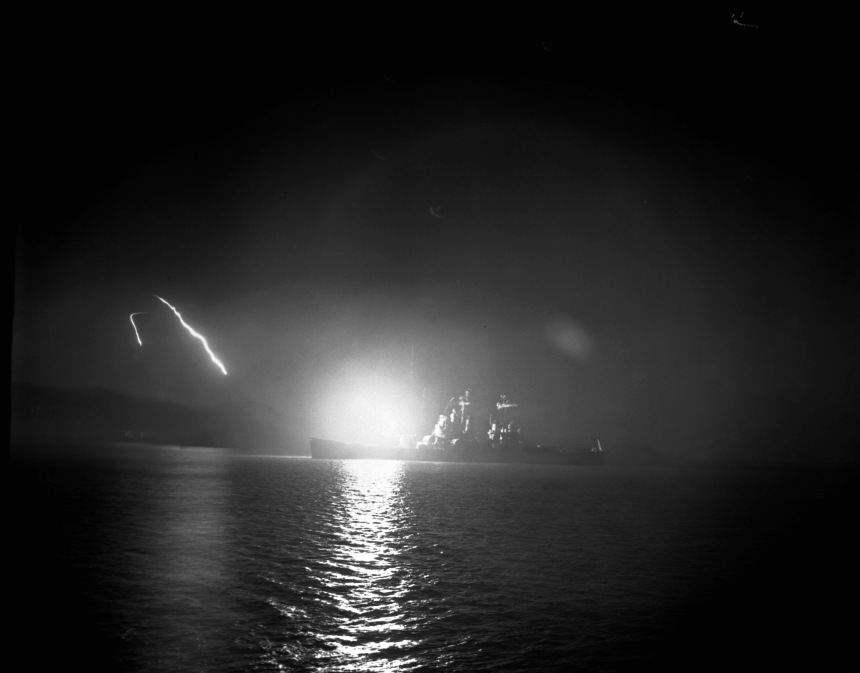 Heavy cruiser USS Saint Paul (CA-73) lights up the night while firing her 8 inch guns off the coast of Hungnam, North Korea 1950