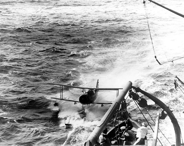 Memphis' Curtiss SOC Seagull scout-observation aircraft hooked onto the recovery mat, in preparation for being hoisted on board, circa early 1942
