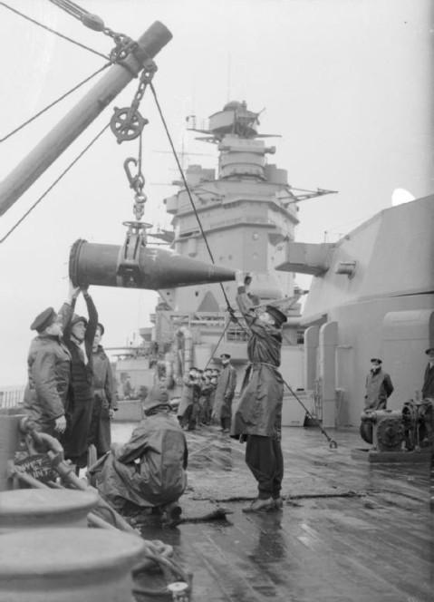 Sailors aboard HMS Rodney receiving a 16-inch shell from an ammunition ship, 1940