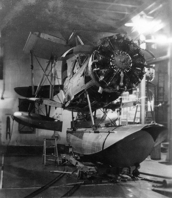 SOC-3 Seagull aircraft stripped for maintenance in the hangar of light cruiser Savannah, 1938; note the close up of the Pratt and Whitney R-1340 9-cylinder radial engine and caster tracks to roll the planes out of the hangar on its truck and on deck for launch NH 85630