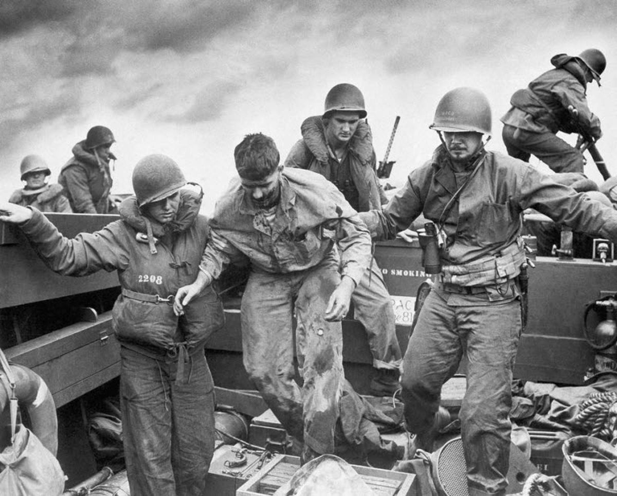 US Coast Guardsmen assisting a wounded Marine into an LCVP after the Marine's LVT sustained a direct hit while heading to the landing beaches on Iwo Jima, Feb 18, 1945.