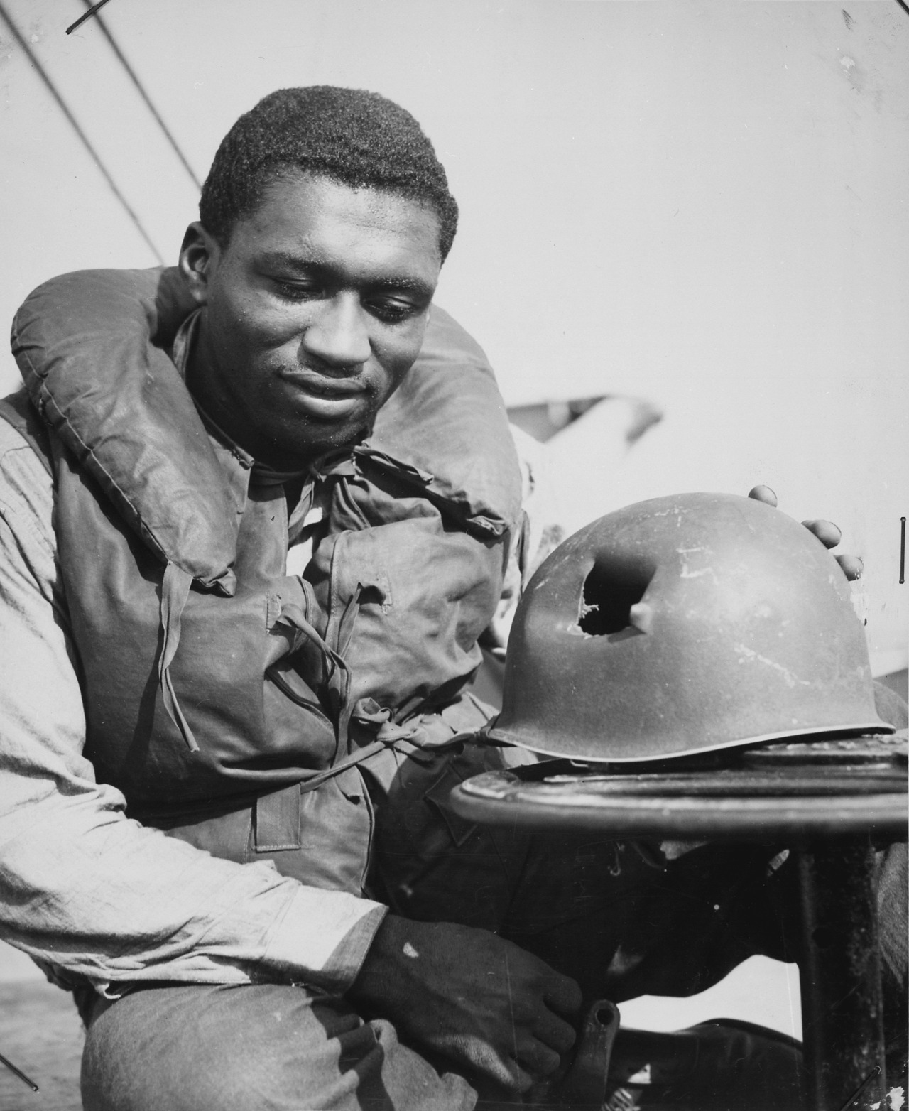 uscg Charles Tyner, Fireman First Class, inspects his helmet hit by shrapnel during the Allied landings in southern France. 1944.