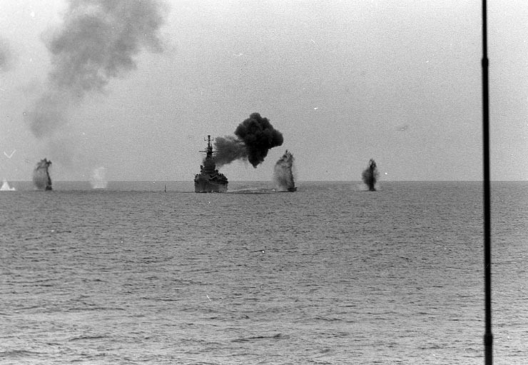 USS Saint Paul bombarding the Cong Phy railroad yard 25 miles south of Thanu Hoa, Vietnam, 4 Aug 1967; note splashes from coastal gun batteries