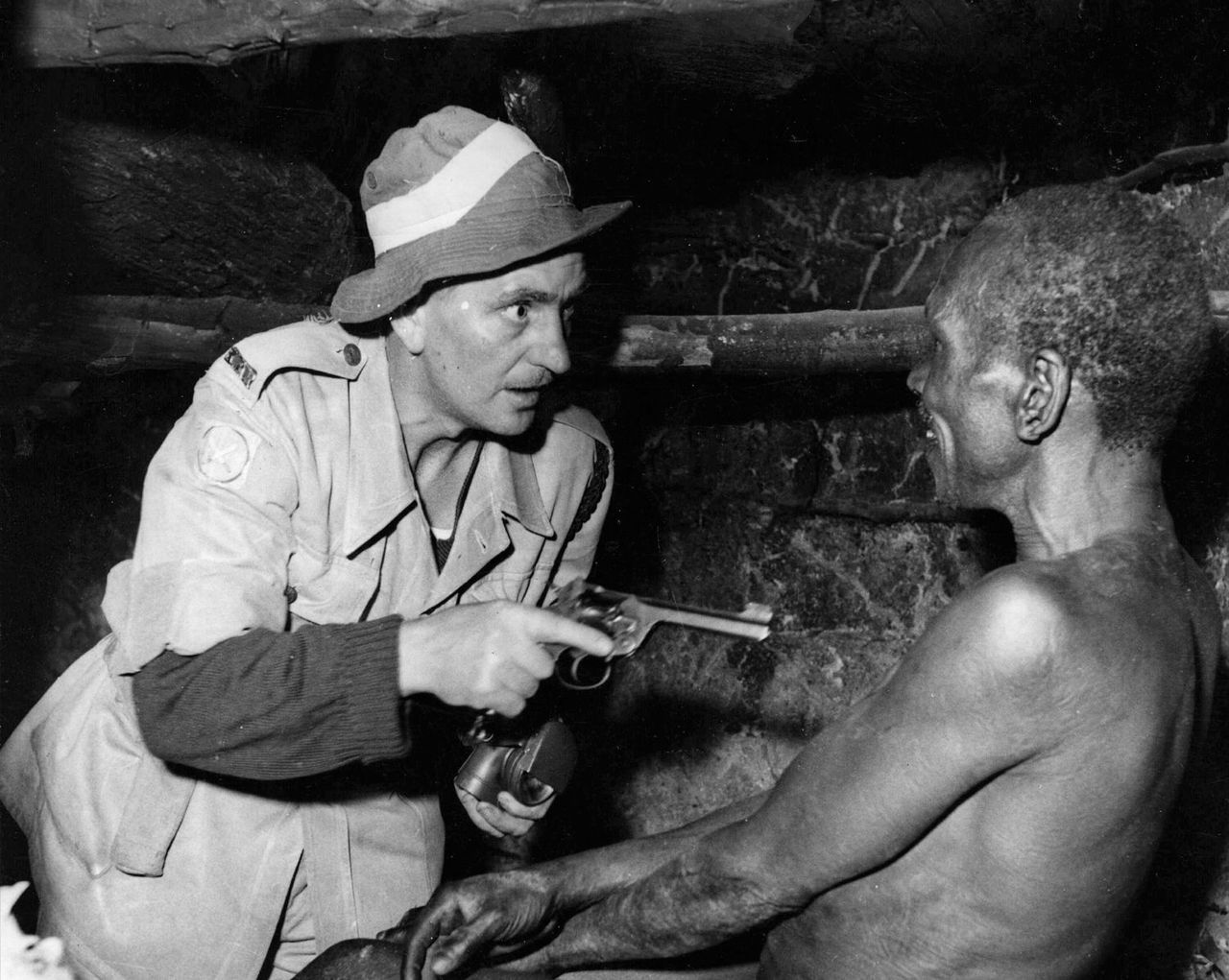 A British officer aims his revolver at a smiling suspected Mau Mau during a night raid. 1952, Kenya note the trigger discipline trigger discpline and the similarity to the depiction from the Trenches above...some things never change
