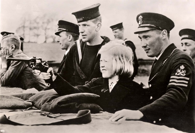 A girl shooting a Webley under the instruction of British sailors, England, 1939