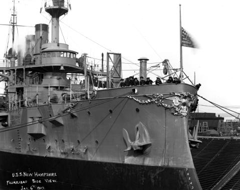 View of the ship's bow decoration, taken while the battleship was in dry-docks at the New York Navy Yard, Brooklyn, New York, 6 January 1909. Note gilt-work on the eagle figurehead and associated decorations, stockless anchors in hause pipe, stocked anchor on billboard further aft, Sailors leaning on the bow bulwark, jack at half-mast, bell mounted in front of the ship's pilothouse, and barred portholes. Photograph from the Bureau of Ships Collection in the U.S. National Archives / USNHC # NH 19-N-4-8-21, via Navsource. Click to very much big up