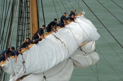 The crew aboard the Coast Guard Cutter Eagle work to take in the sails as the ship heads to Corpus Christi, Texas, July 2, 2010. Crewmen work in the rigging nearly 100 feet above the water. U.S. Coast Guard photo by Petty Officer 2nd Class Patrick Kelley.