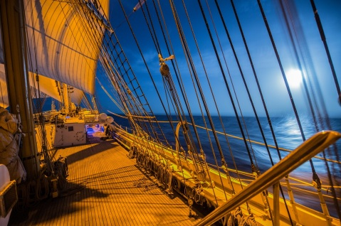 The Coast Guard Cutter Eagle sails through the ocean as the moon's reflection beams across the sea. (U.S. Coast Guard photo by Petty Officer 2nd Class Walter Shinn)