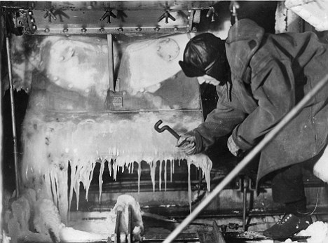 Chipping away ice on the deck of H.M.S. Vansittart on convoy escort duty in the Arctic feb 1943
