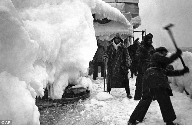 Chipping away ice on the deck of H.M.S. Vansittart on convoy escort duty in the Arctic