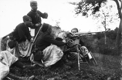 Posed shot of french zouaves firing hotchkiss machinegun note the assistant gunnner catching brass in canvas feedbucket