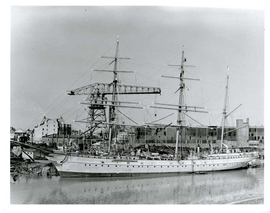 The Coast Guard Cutter EAGLE laying at a shipyard in Bremerhaven, Germany, 1946, being rigged and outfitted for her voyage to the United States. Note bombed out buildings in background