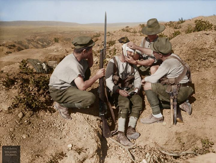 Australian soldiers dressing the head wound of an injured comrade with his first aid field dressing, Gallipoli peninsula, Turkey, 1915.