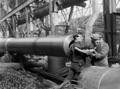 These were really big guns: Worker being helped out of a BL 15 heavy gun after she had finished cleaning the rifling, Coventry Ordnance Works, England, United Kingdom .