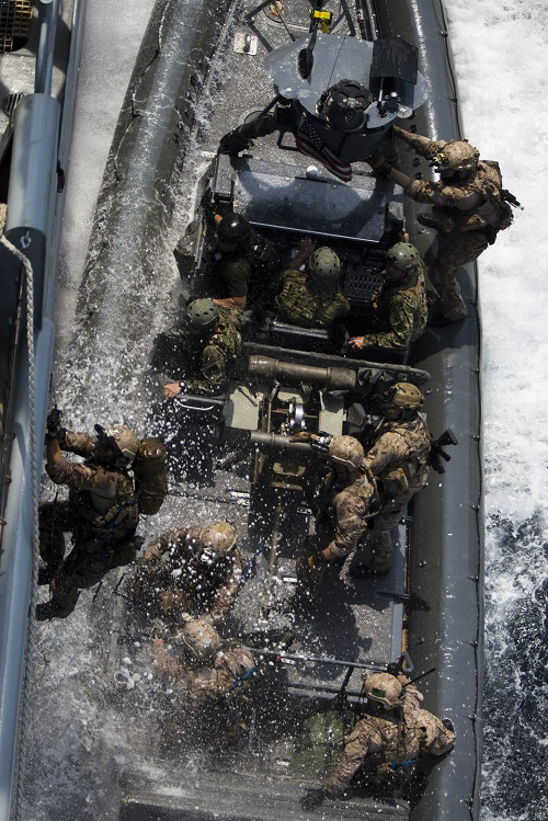 U.S. Navy SEALs board a ship from a Rigid-Hull Inflatable Boat as they conduct a joint Visit, Board, Search, and Seizure (VBSS) exercise alongside U.S. Marines assigned to Force Reconnaissance Platoon, Maritime Raid Force, 26th Marine Expeditionary Unit (MEU), during composite training unit exercise (COMPTUEX) in the Atlantic Ocean, July 20, 2015. (U.S. Marine Corps photo by Cpl. Andre Dakis/26th MEU Combat Camera/Released)