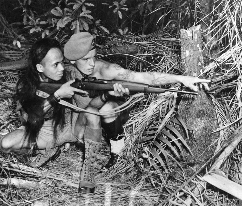 Sergeant R Beaumont of the King's Own Yorkshire Light Infantry (KOYLI), attached to the Malay Regiment, instructs a Dyak tracker in the use of modern firearms.